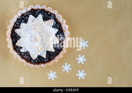 Weihnachten-Hackfleisch-Kuchen, mit einem Stern verziert und mit Puderzucker auf Goldgrund abgestaubt - Stockfoto