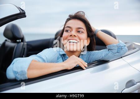 Lächelnde Brünette Frau ruht in ihrem Cabriolet parkte am Strand - Stockfoto