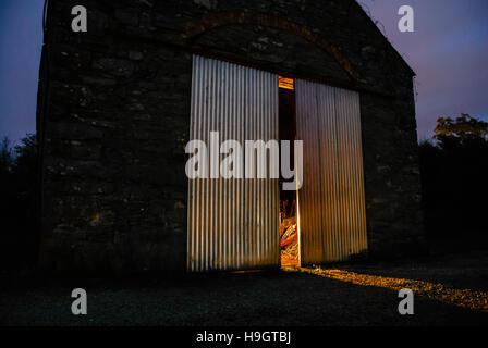 Licht leuchtet, aus halb offenen Türen von eine alte irische Stein Scheune in der Nacht - Stockfoto