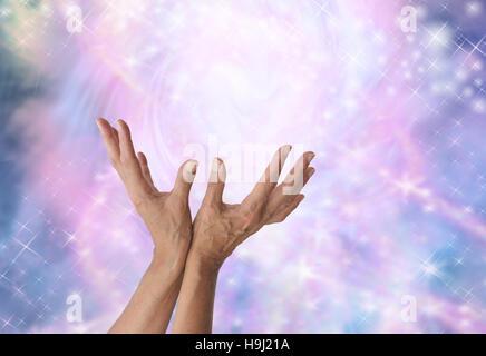 Weibliche Energie Arbeiter mit Hände ausgestreckt und öffnen nach oben sensing spektakuläre heilende Energie sanft - Stockfoto
