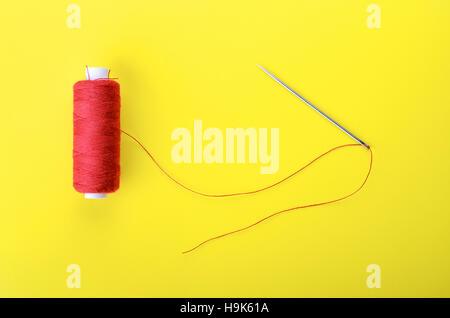 Roter Faden und Nadel auf gelbem Grund, Symbol der Handarbeit und ...