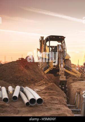 Planierraupe Carving Loch für Rohrverlegung bauseits Konstruktionen. Ende der Arbeit Tag Sonnenuntergang. - Stockfoto