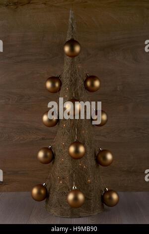 Dekorative Weihnachtsbaum gemacht aus Stroh mit goldenen Kugeln auf hölzernen Hintergrund isoliert - Stockfoto