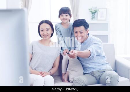 Eine glückliche Familie von drei im Wohnzimmer vor dem Fernseher - Stockfoto
