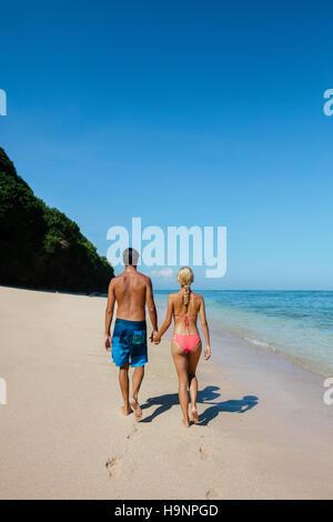 Rückansicht-Schuss von paar in den Flitterwochen Hand in Hand zu Fuß entlang der Küste. Paar in Liebe erholsamen - Stockfoto