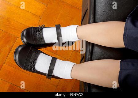 Junge Schule Studentin mit schwarze Schuhe und weiße Socken, Standortwahl auf einem Ledersofa - Stockfoto