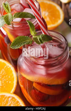 rote Sangria mit Orange, Erdbeere und Heidelbeere Makro in einem Glas auf dem Tisch. vertikale - Stockfoto