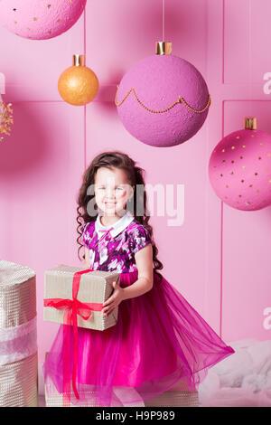 Brünette Mädchen Kind 5 Jahre alt in einem rosa Kleid. in Rosenquarz Ferienzimmer mit Geschenken - Stockfoto