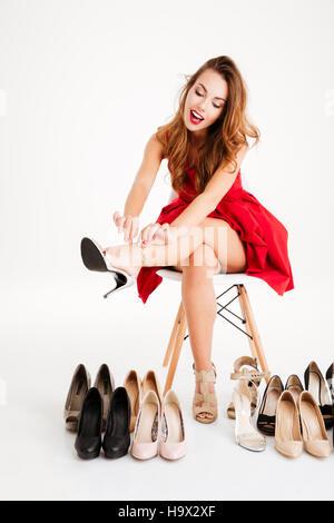 Porträt einer glücklich begeistert Frau im roten Kleid sitzt und versucht, auf ihre neuen high Heels Schuhe in weißem - Stockfoto