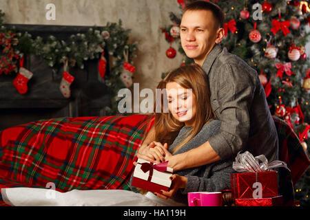Liebespaar und Weihnachten. Mädchen umarmt Freund. Sie hält ein Weihnachtsgeschenk. Im Hintergrund, einen schönen - Stockfoto