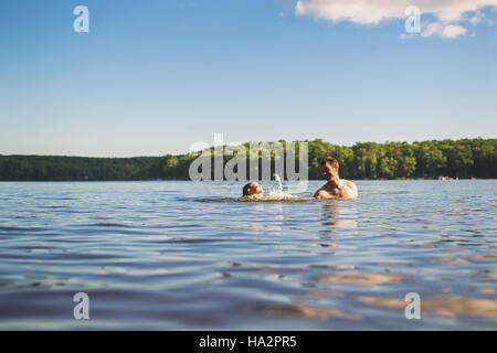 Vater lehrt seinen Sohn in einem See schwimmen - Stockfoto