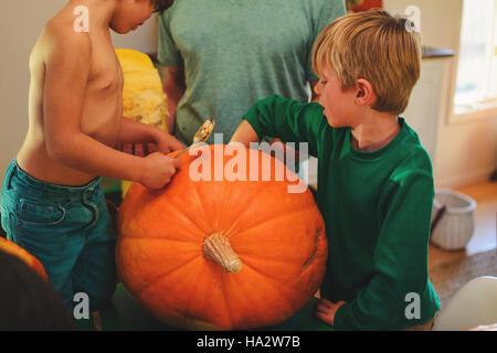 Vater und zwei Söhne schnitzen Kürbisse für Halloween - Stockfoto