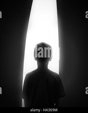 Eine schwarze und weiße Silhouette eines kleinen Jungen auf der Suche in einem hellen weißen Fenster für ein Konzept - Stockfoto