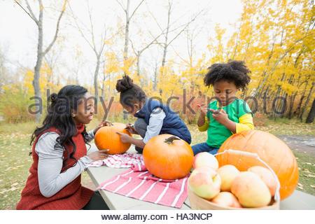 Mutter und Töchter schnitzen Kürbisse auf Picknick-Tisch im Herbst park - Stockfoto