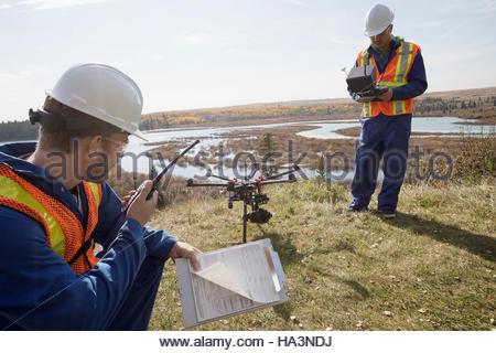 Vermesser mit Drohne Ausrüstung und Walkie-talkie auf sonnigen Hügel mit Blick auf See - Stockfoto