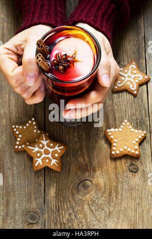Weihnachten-Heißgetränk - Glühwein in weiblichen Händen mit Zimtstange, Sternanis und festliche Weihnachten Lebkuchen - Stockfoto