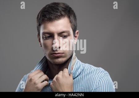 Intensive launisch Porträt des jungen Stoppeln Mann hält Kragen hinter über die Schulter schauen - Stockfoto