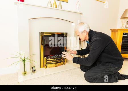 OAP, warme wärmende Hände in der Nähe von Feuer, die Rechnungen zu halten zu halten versuchen leisten nicht Heizung - Stockfoto