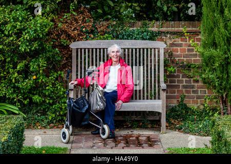 Eine ältere behinderte Frau sitzt auf einer Bank, Sussex, UK - Stockfoto