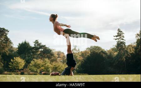 Passen Sie junges Paar beim Acro Yoga im Park. Mann auf dem Rasen liegen und Frau in seinen Füßen balancieren. - Stockfoto