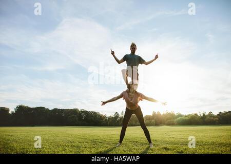 Starke junge paar akrobatische Yoga machen Übung im Park. Mann auf Rückseite der Frau stehen und balancieren. - Stockfoto