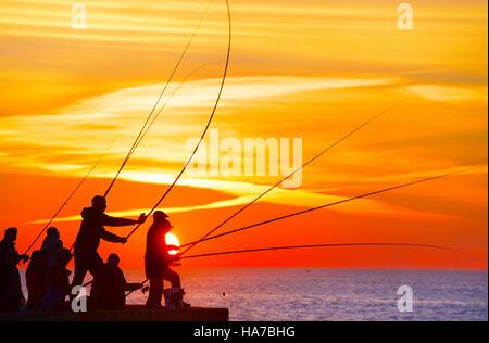 Gruppe von Fischer auf einem Pier bei Sonnenuntergang. Porto, Portugal - Stockfoto