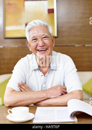 Senior asiatischen Mann liest ein Buch oder ein Dokument im Arbeitszimmer - Stockfoto