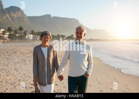 Porträt von einem senior Brautpaar bei einem Spaziergang am Strand zusammen. Älteres Paar Hand in Hand und Wandern - Stockfoto