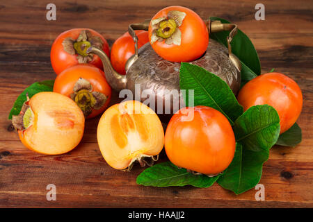 Reife Kaki Früchte mit Vintage Teekanne. Orientalische Osten persische Stillleben. - Stockfoto