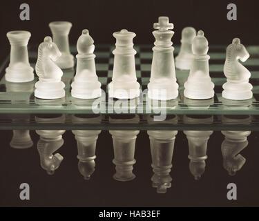 Alte Glas Schachfiguren an Bord reflektiert auf schwarz leicht strukturierten Hintergrund - Stockfoto