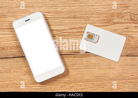 Smartphone mit leeren Bildschirm und Handy GSM-SIM-Karte auf dem Tisch, Ansicht von oben - Stockfoto