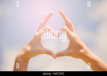 Symbol der Liebe, menschliche Hände in Herzform gegen blauen Himmel - Stockfoto