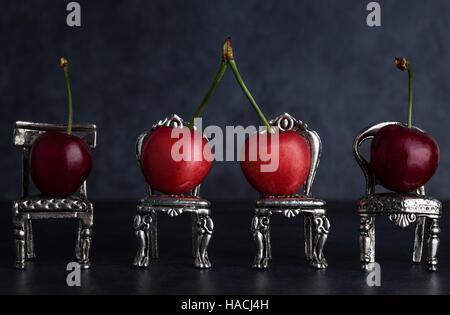 Vier rote köstliche Kirschen gelegt auf winzigen Vintage Silber Stühlen auf dunklem Hintergrund mit Textfreiraum - Stockfoto