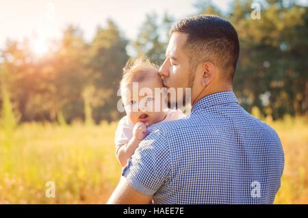 Junger Papa küssen ein Baby. Laufen Sie Herbstabend im Freien. - Stockfoto