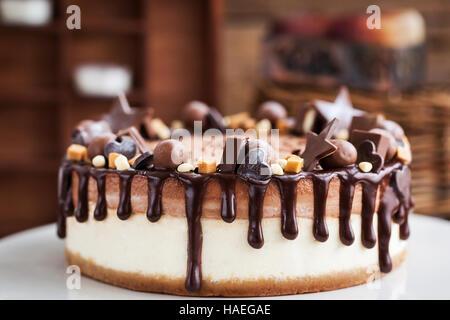 Köstliche doppellagige Schokoladen-Käsekuchen mit Süßigkeiten und Zuckerguss verziert - Stockfoto