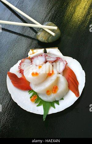 Jakobsmuschel-Sashimi serviert auf einer Jakobsmuschel in einem japanischen Restaurant. - Stockfoto