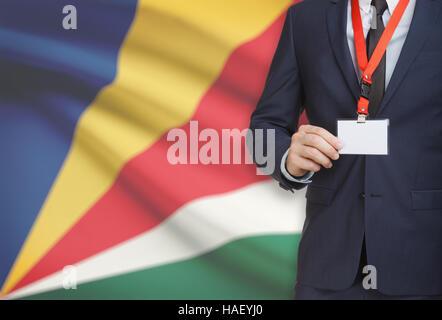 Geschäftsmann, ein Schlüsselband mit einer Flagge auf Hintergrund - Seychellen Karte Namensschild festhalten - Stockfoto