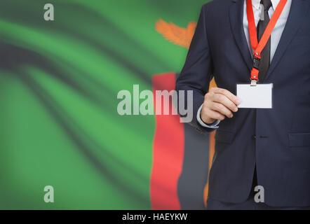 Geschäftsmann hält Namensschild Karte auf ein Schlüsselband mit einer Flagge auf Hintergrund - Sambia - Stockfoto