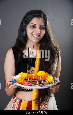ein Mädchen lächelnd und halten eine traditionelle Diwali Thali Mumbai Maharashtra, Indien - Stockfoto