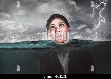Asiatische Geschäftsfrau mitten im Meer ertrinken. Depression-Geschäftskonzept - Stockfoto