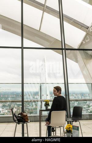Frau allein an einem Tisch sitzen, an einem kühlen bar genießen Sie die spektakuläre Aussicht auf die Scherbe aus - Stockfoto