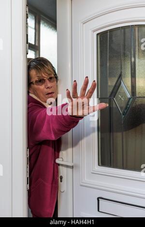 Frau versucht, einen Eindringling wegzudrücken. - Stockfoto