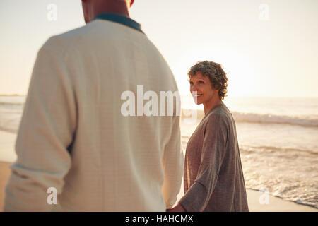 Lächelnde ältere Frau mit ihrem Mann am Strand entlang spazieren. Älteres Paar zusammen am Meer spazieren. - Stockfoto