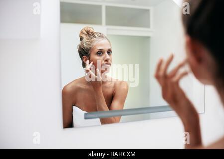 Schöne junge Frau steht im Badezimmer. Weibliche Blick in den Spiegel und berühren ihre Gesichtshaut. - Stockfoto