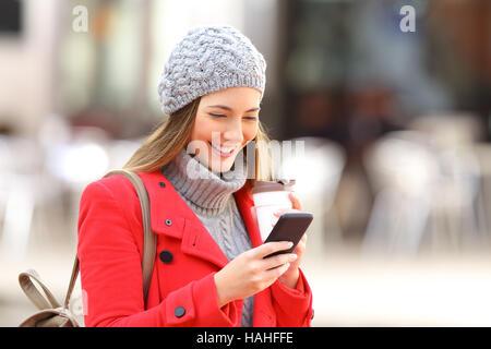 Glücklich Mode Frau mit einem smart-Phone und hält einen Take away Kaffee auf der Straße im winter - Stockfoto