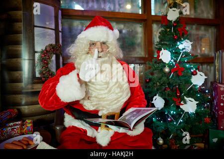 Santa in Grotte Display beleuchtet Weihnachten Weihnachtsbaum, Geschenke, Kamin, Strümpfe begabt gewickelt lesen - Stockfoto