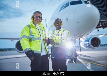 Porträt zuversichtlich Luft Verkehr Kontrolle Bodenpersonal Arbeiter in der Nähe von Flugzeug am Flughafen Rollfeld - Stockfoto