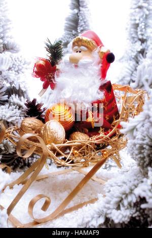 Santa Claus Figur sitzt auf einem goldenen Schlitten in einem verschneiten Wald - Stockfoto