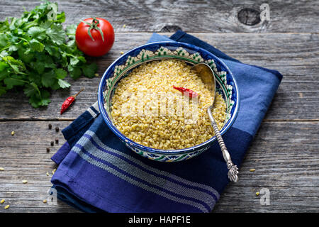 Rohe Bulgur Weizenkörner in bunten arabischen Schale, frische Petersilie, Tomaten und Paprika zum Kochen. Holztisch - Stockfoto