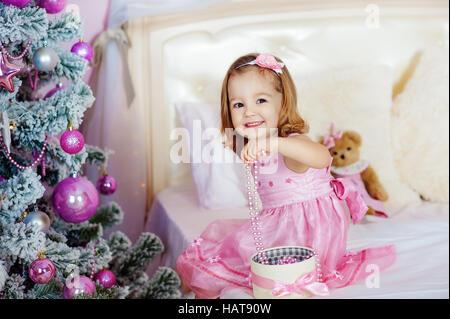 Sehr schöne charmante kleine Mädchen Blonde in rosa Kleid, sitzt auf einem Kinderbett und lacht laut den Hintergrund - Stockfoto